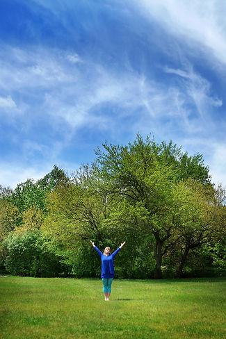 Jody standing in salute yoga pose under beautiful blue skies