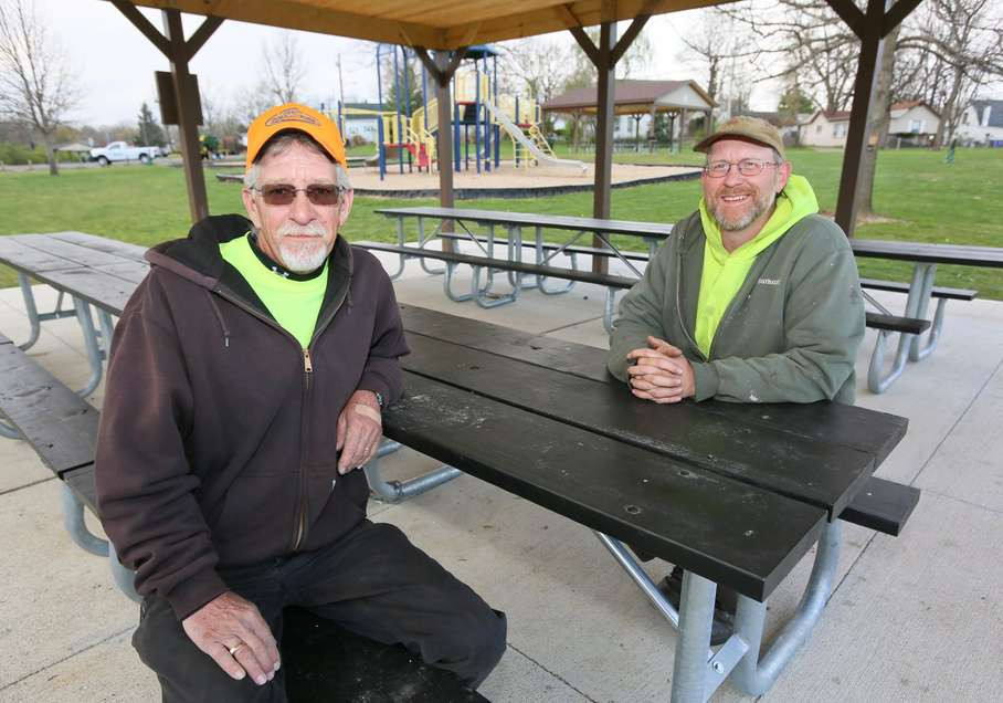 Terry Scrivner and Kevin Clements of the Hamilton Parks Conservancy sit at the new picnic tables under a new shelter at Crawford Woods. GREG LYNCH