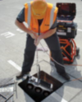 Technician lowering Proteus crawler into drain