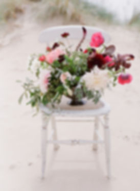 Fine art coastal wedding inspiration styled shoot | Beautiful floral centrepiece in deep reds and blush | Design and styling by Yorkshire wedding planner Rosy Apple Events | Julie Michaelsen Photography