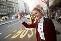 Businesswomen hailing taxi downtown.jpg