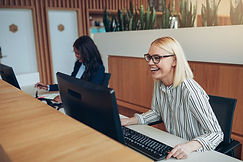 Laughing young businesswoman working on