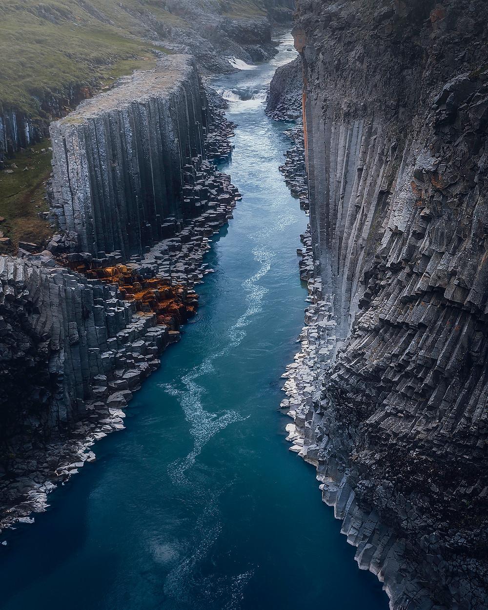 Dronebilde av en basaltsteincanyon øst på Island, som deler av året har veldig fargerikt vann.