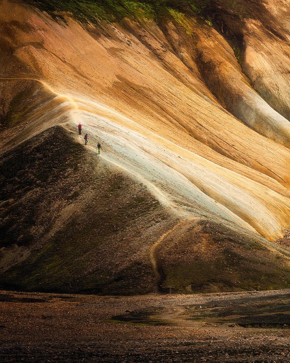 Tre vandrere på tur ned det fargerike landskapet i Landmannalaugar.