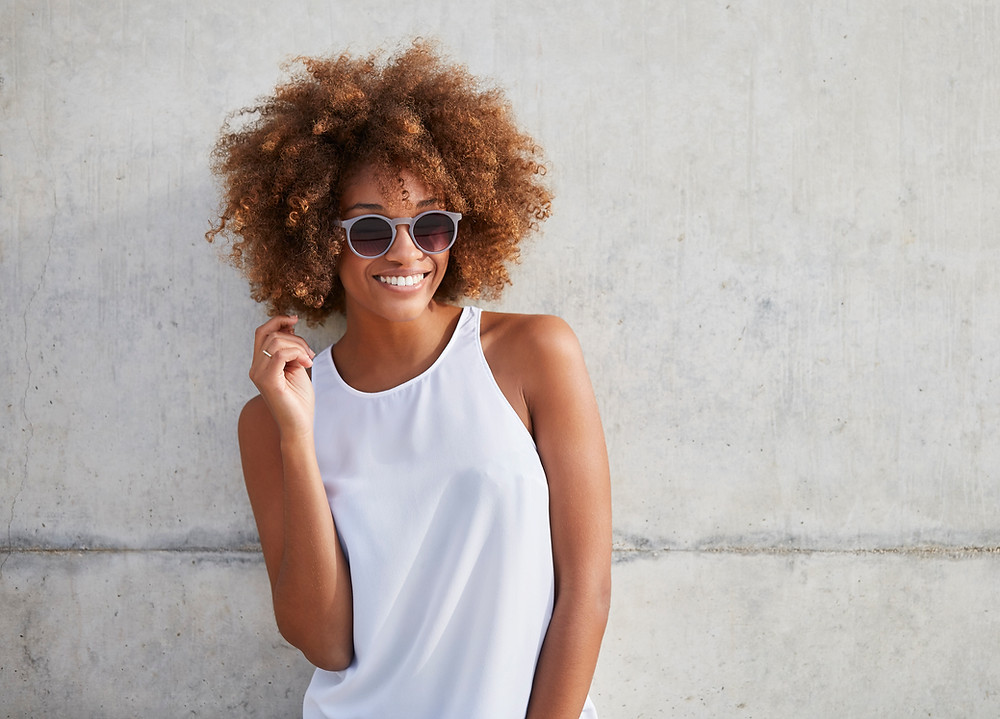 young woman wearing shades and a white top looking off to the side while smiling