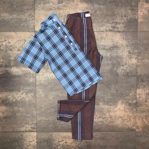 """Camicia bimbo """"Otto"""" con collo alla coreana a manica corta in cotone.  Pantalone """"Leo"""" con pence in lino scozzese marrone e blu."""