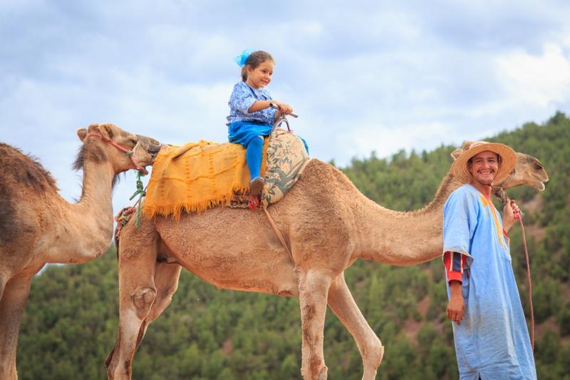 מוסיא רוכבת על גבי גמל בהרי האטלס