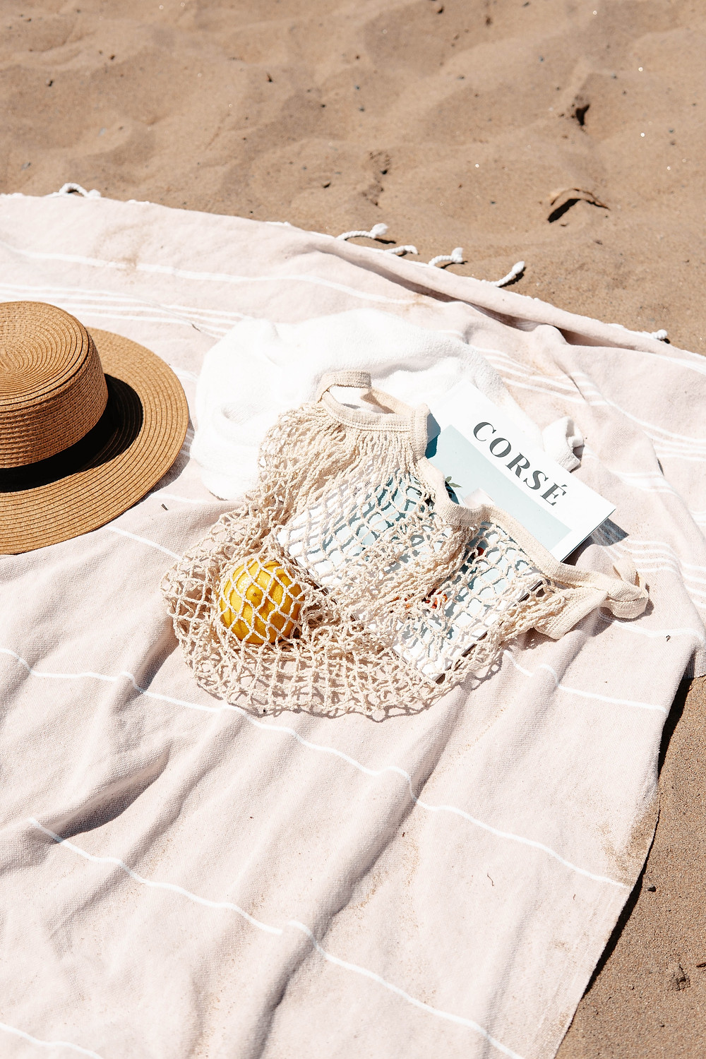 beach blanket on the sand with a hat and a reusable product bag containing a fruit and a magazine