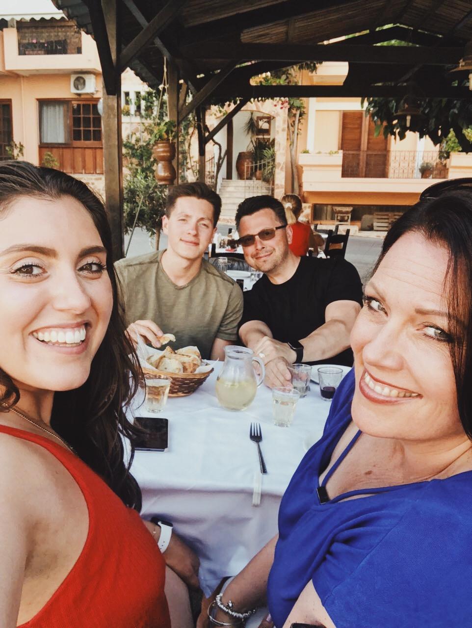 Marika smiling and taking a selfie of her and her travel companions enjoying a meal