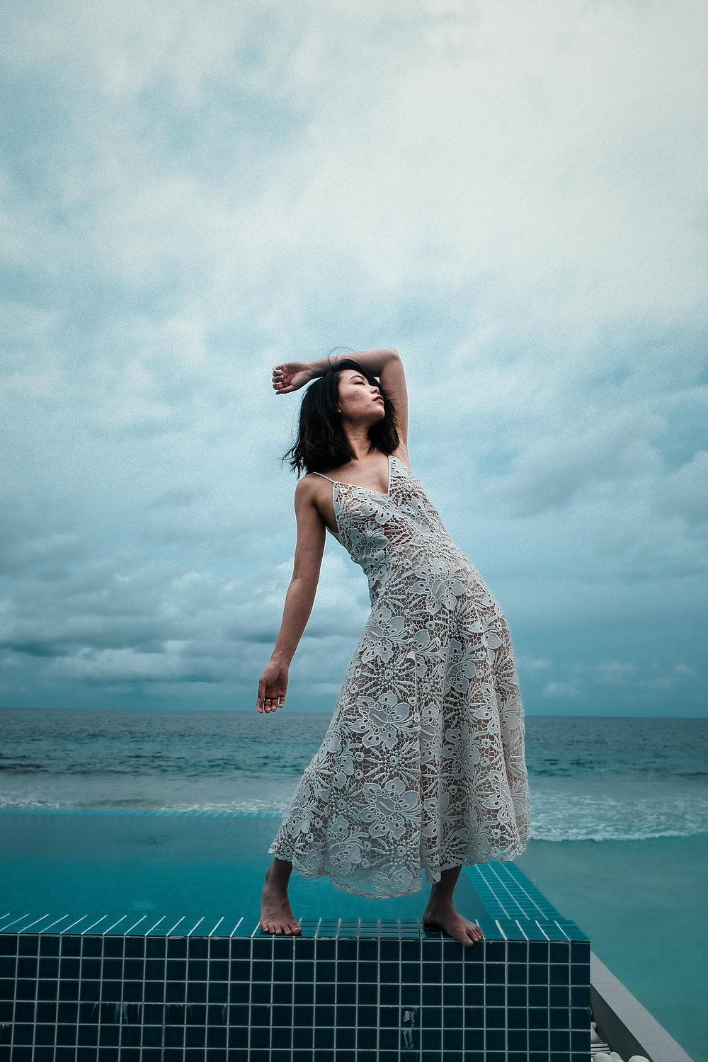 asian woman with shoulder length dark hair wearing a lacey spaghetti strap sundress dramatically dances on the edge of a pool next to the ocean in this shoot for trade image