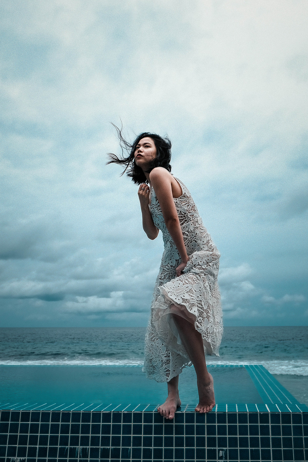 asian woman wearing a lacey cream dress dances on the edge of a pool with the wind whipping her hair in this shoot for trade image