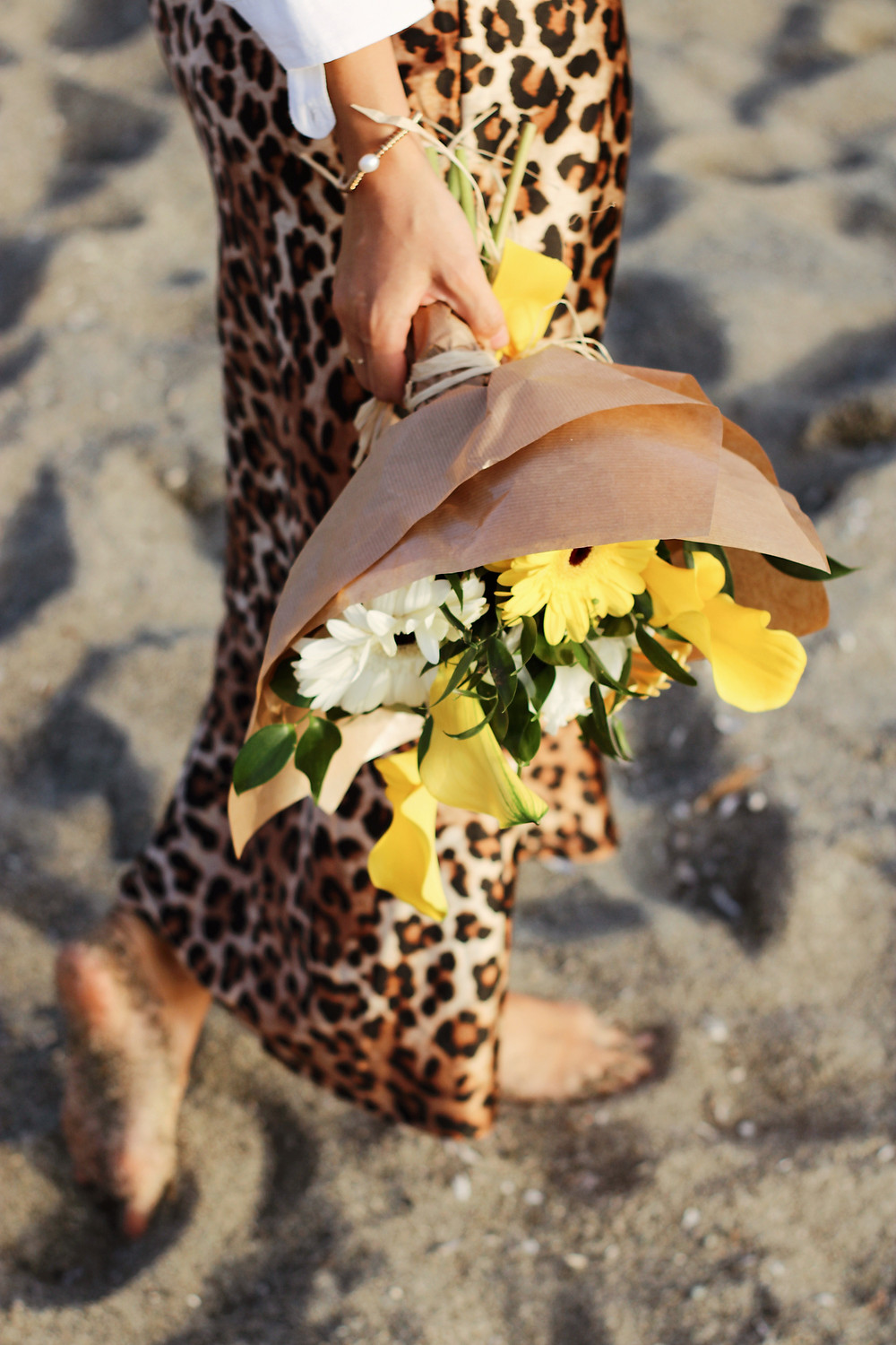 lower body of a woman wearing animal print skirt with bare feet walking in the sand with a bouquet of flowers in her hand