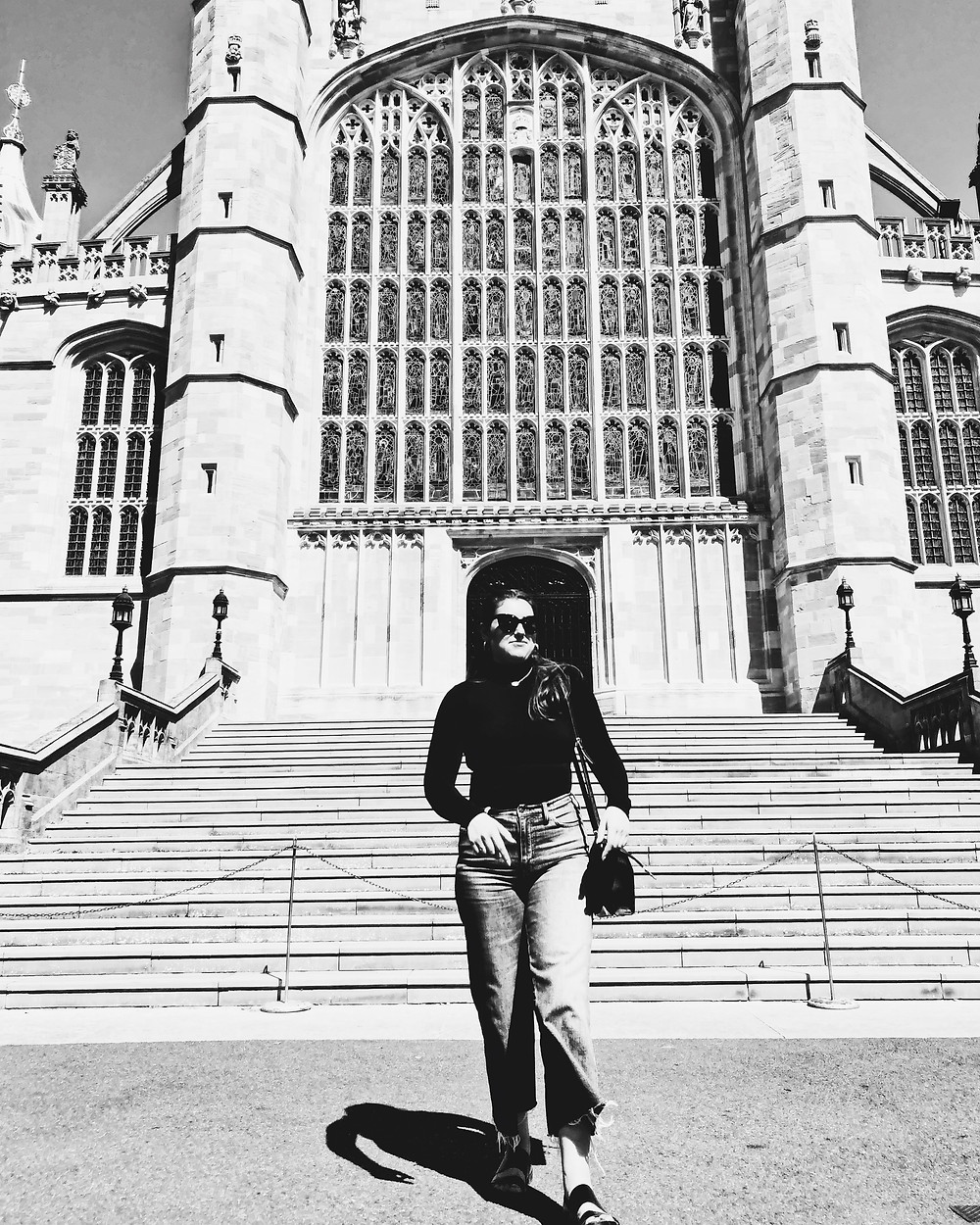 a black and white photo of Marika standing in front of an old church with sunglasses on
