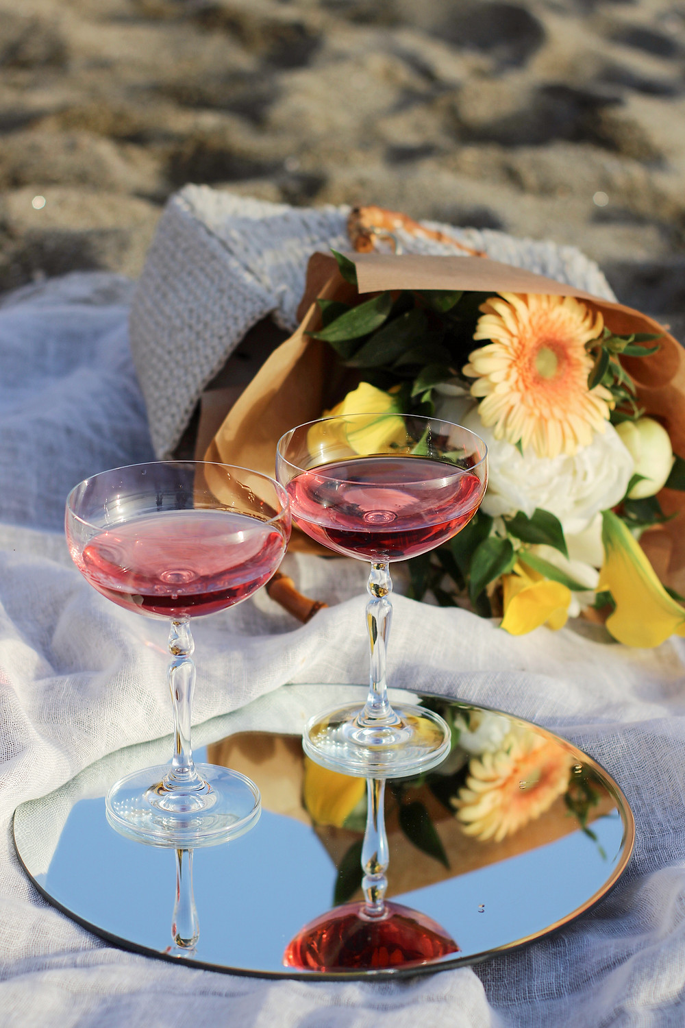 martini glasses on a mirror with pink liquid inside beside some flowers resting on a blanket on a beach