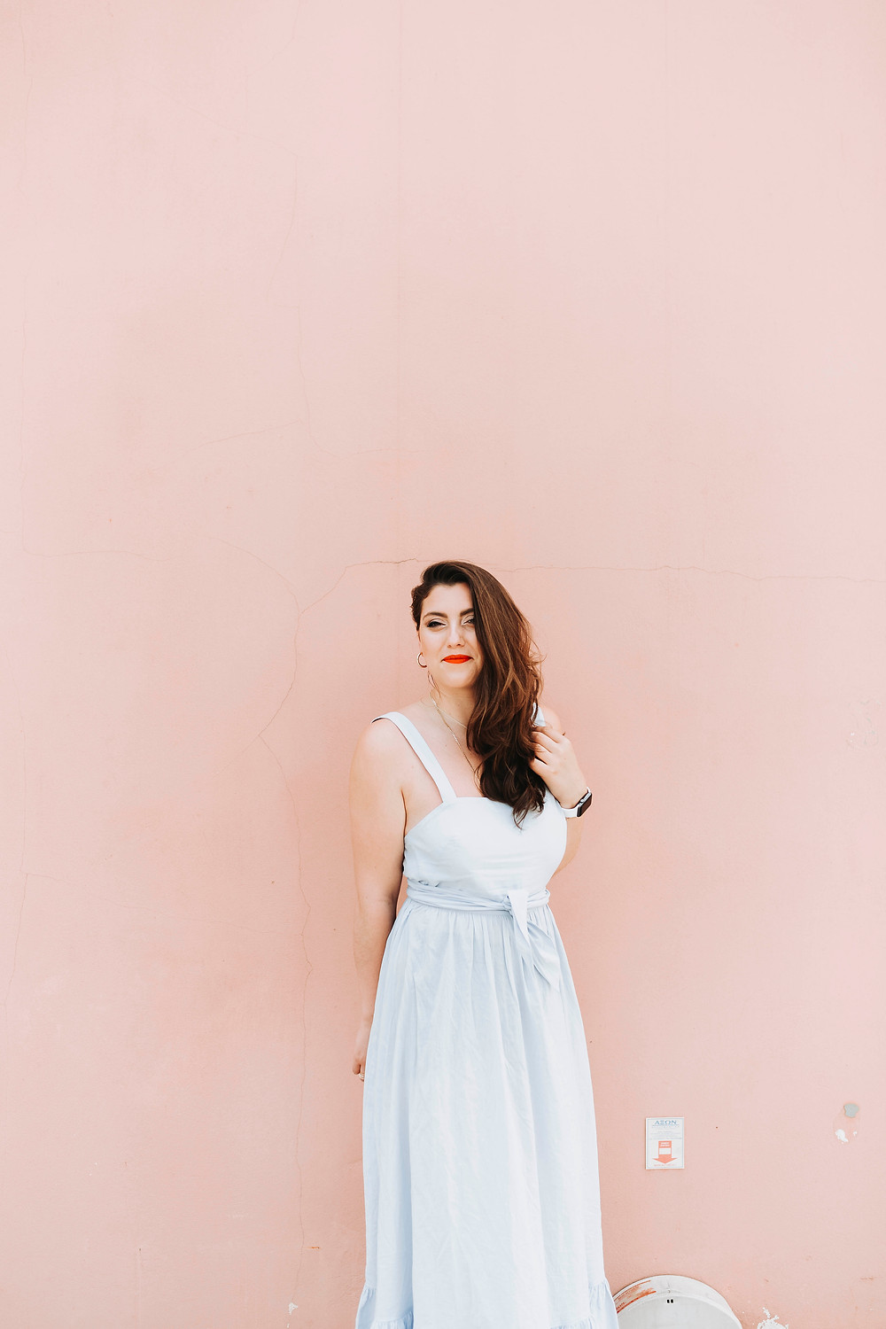 Marika standing in a white dress in front of a pink wall with red lipstick smiling