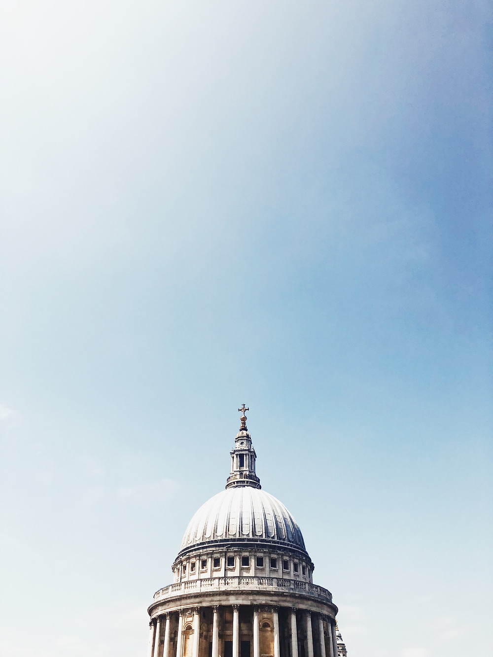 The top of St. Pauls Cathedral in London with a bright blue sky behind it