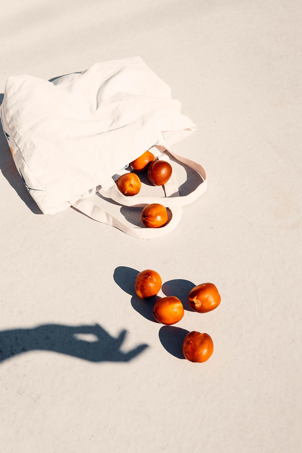 oranges falling out of a canvas bag to the ground with a shadow hand shown reaching out to them as an example on how creatives can use engaging images to use social media
