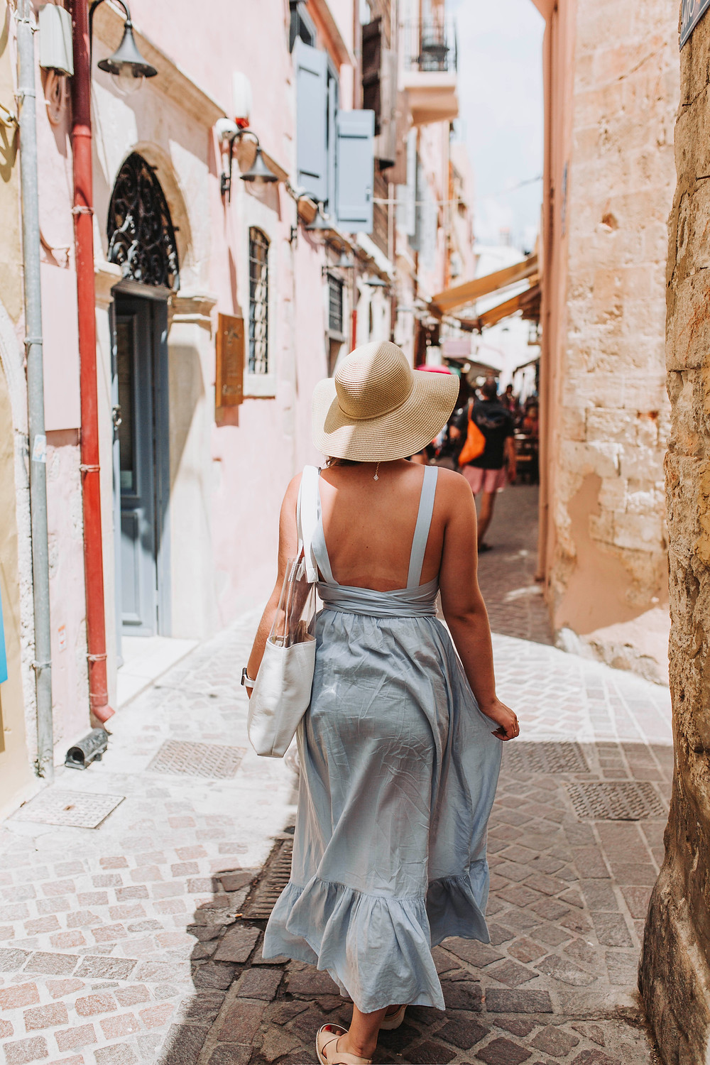 Marika walking down a side street on her travels in a blue dress and cream-colored hat
