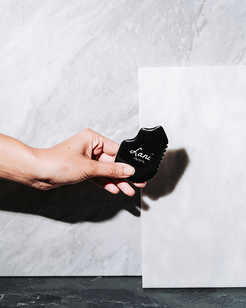 photographer using shadows and backdrops to make product photo of massage stone stand out