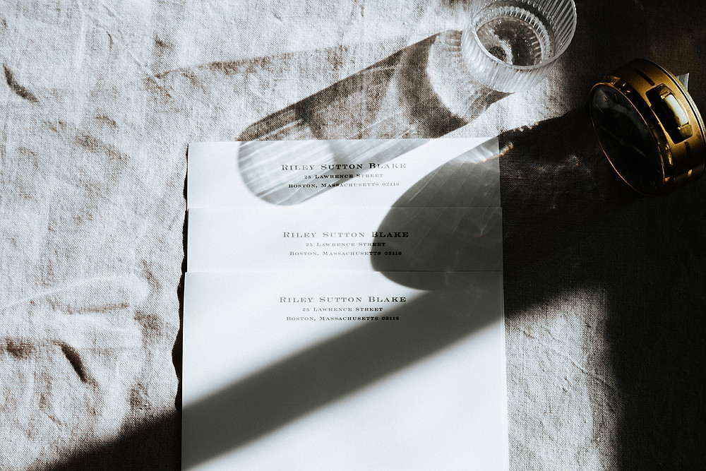 overhead view of white stationary paper with a glass of water beside it