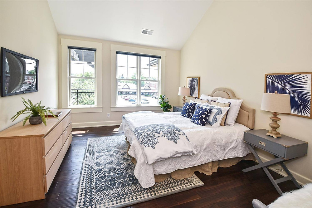 an image of a well-designed staged bedroom by Nest Home Staging and Design showcasing how to style pillows