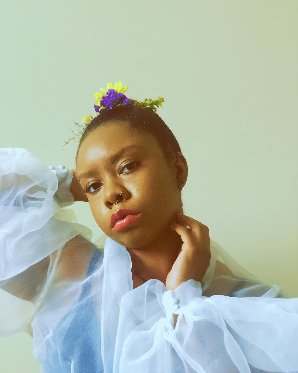 Picture of Kameryn, a black woman with a gauzy white shirt and flowers in her hair.