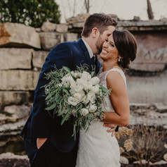 Newlyweds snuggling up outside of wedding venue Bella Sala in Tiffin Iowa while showing off a beautiful bouquet