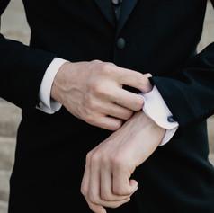 Groom adjusts sleeves and cufflinks.