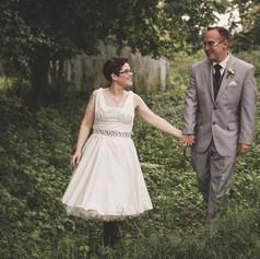Bride and groom walking through foliage on wedding day.