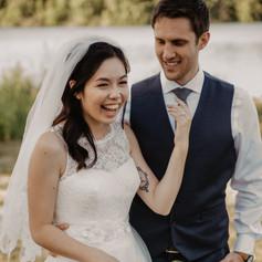 Bride laughs as her photo is taken alongside her groom. Lake Darling in Iowa