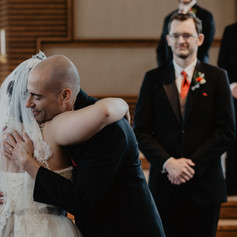 Father of the bride gives daughter away at beautiful indoor ceremony.