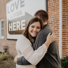 Love Lives Here sign pointing to embraced engaged couple Jenna and Cody