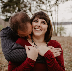 Newly engaged couple, Sara and Trever, cuddling up by Lake MacBride for their engagement photos.