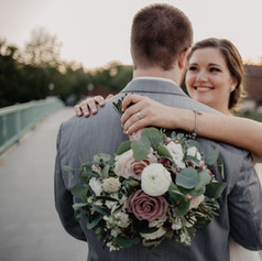 Bride smiling at her groom while bouquet and ring are photographed.