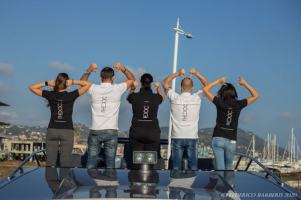 The Doc Staff showing the back of the T-shirt with the logo THE DOC. In the background the port of Imperia Porto Maurizio and the blue sky