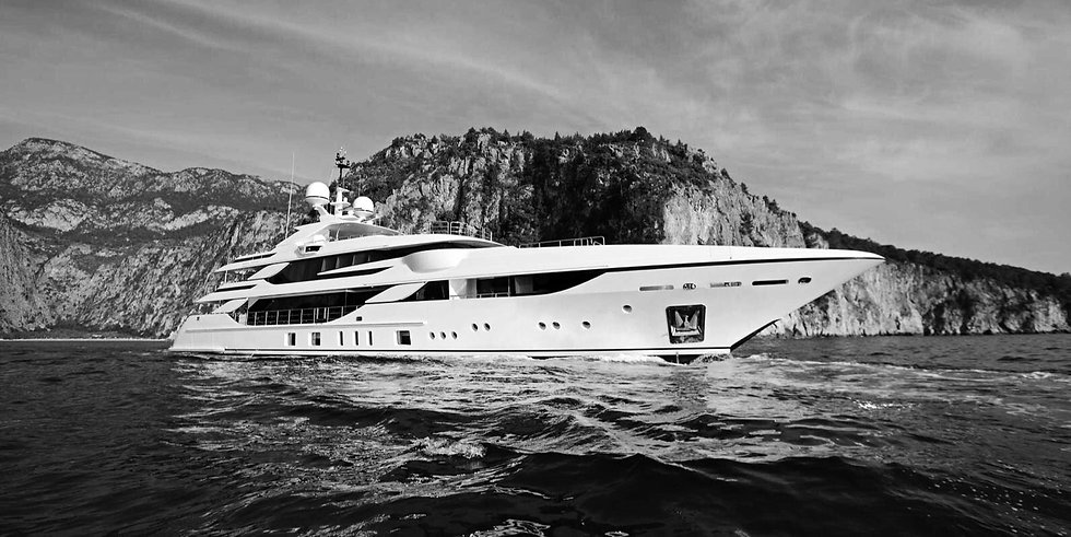 white Yacht. Black and white photo, the sea is calm and behind there is the cliff
