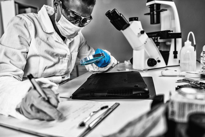informatico forense per indagini digitali esamina un computer al microscopio