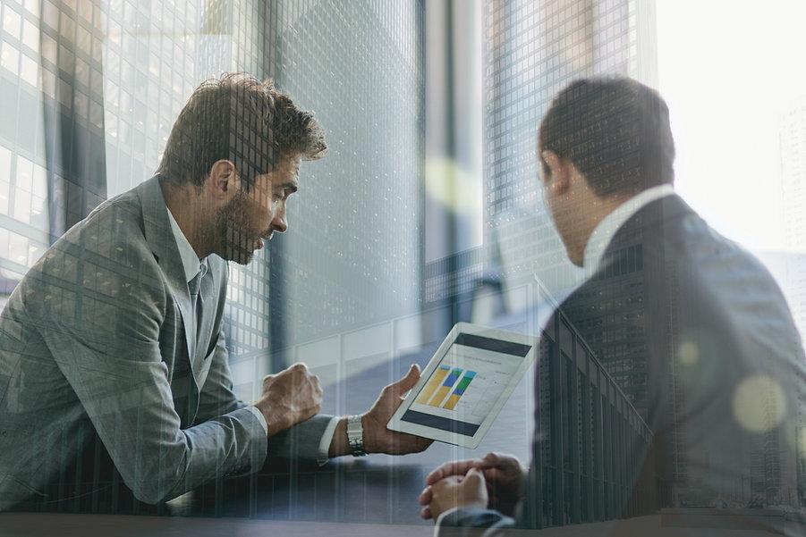 Dois colegas avaliam um gráfico exposto num tablet.