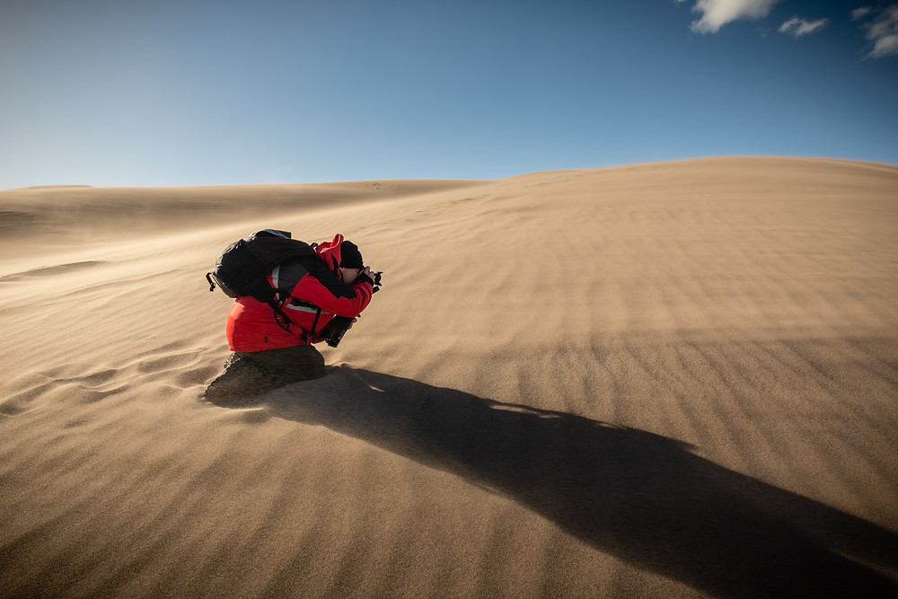 Alan Berhman taking a photo of the Great Sand Dunes in crazy blowing wind and sand