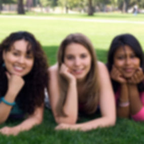 Three women of different racial ethnicities together laying on the ground