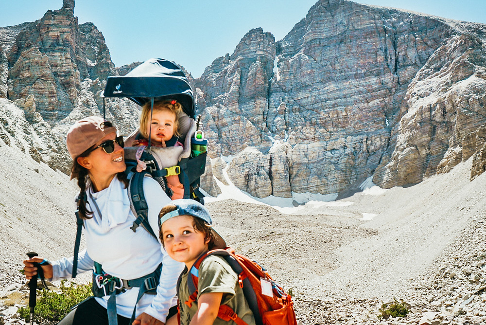 Mom hiking with her kids. One kid in a hiking carrier and the other with a backpack on his back with beautiful mountainous scenery in the background
