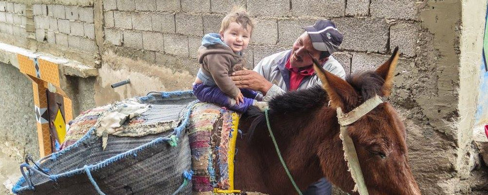 Our baby son on a mule with the owner while on a trek in Morocco