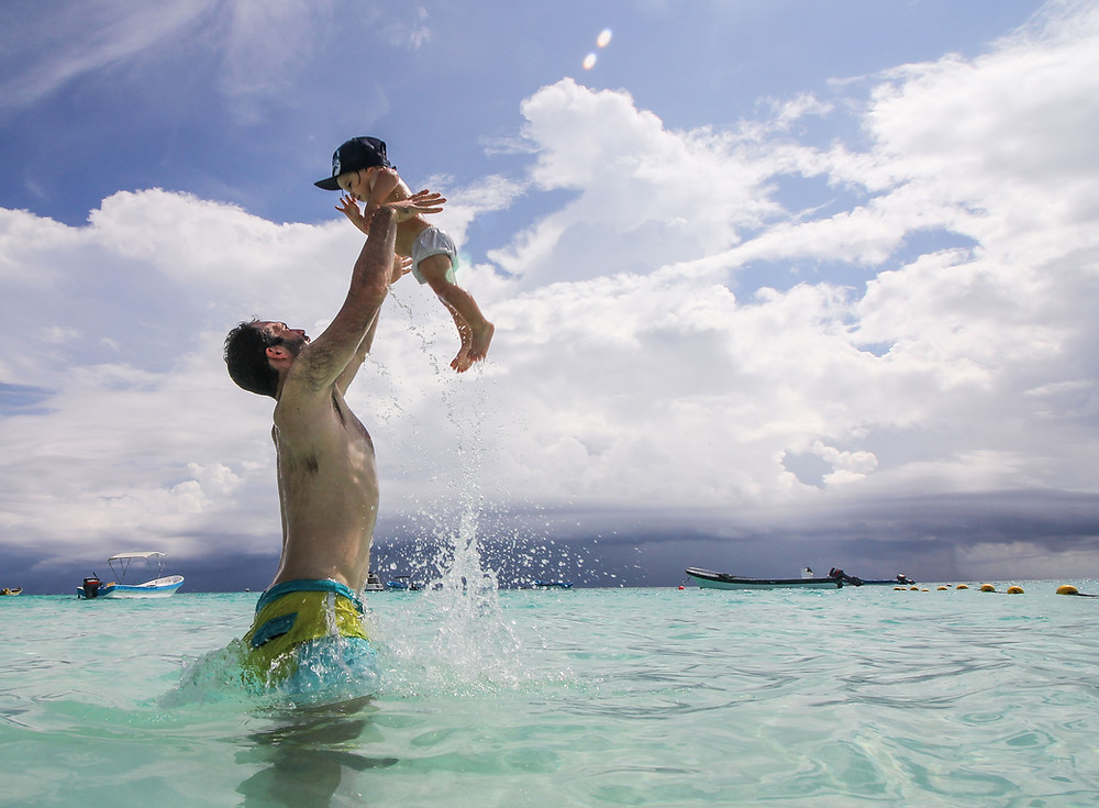 The beach in Tulum is one of the most beautiful in the world. Dad throwing baby in the air in the ocean.