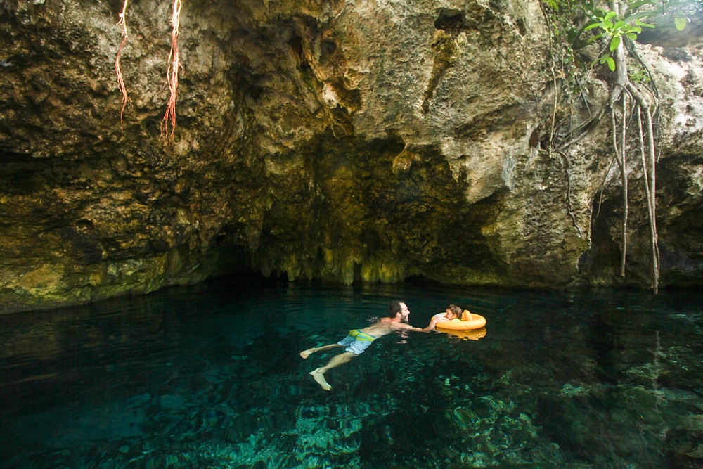 Swimming in the Grand Cenote in Tulum with a baby