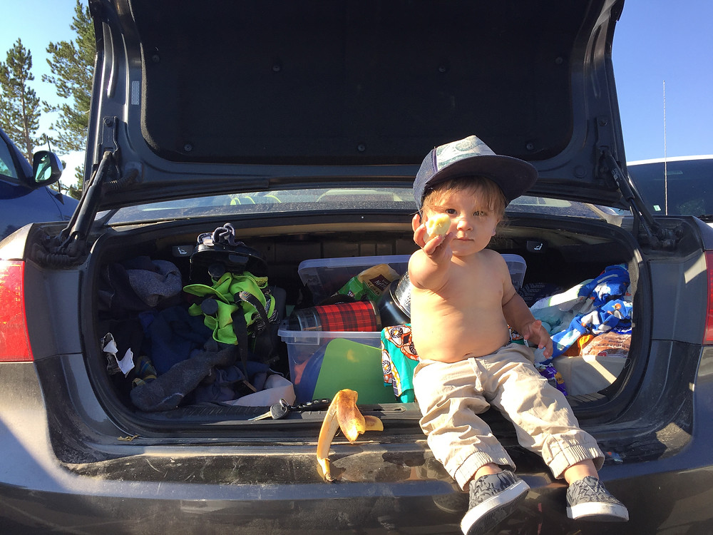 Our toddler hanging out in the trunk of our messy car like a true dirtbag