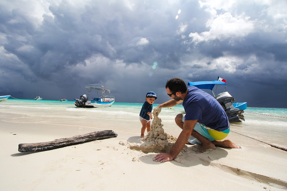Building sandcastles with baby in Tulum, Mexico