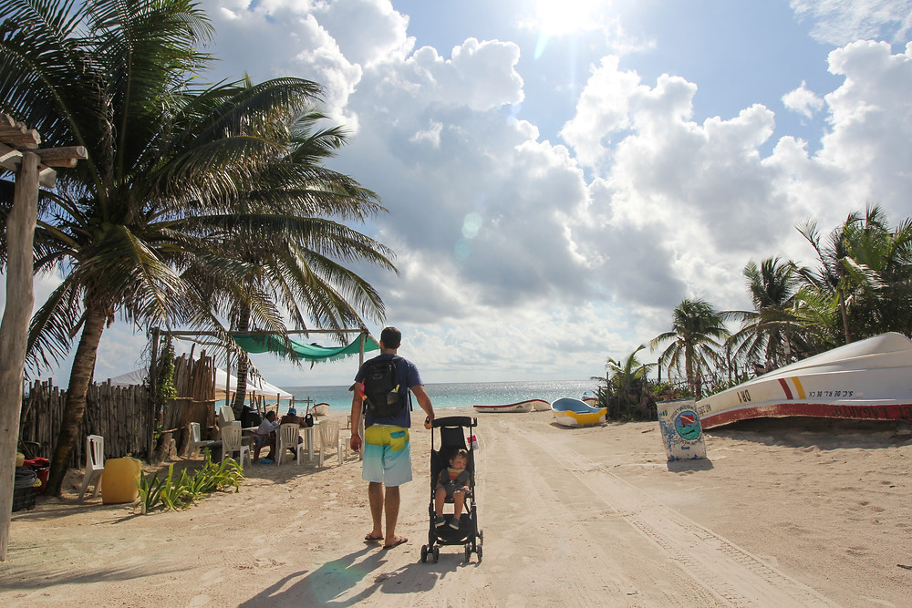 Baby sleeping in his stroller as Dad pulls him down to the beach in Tulum