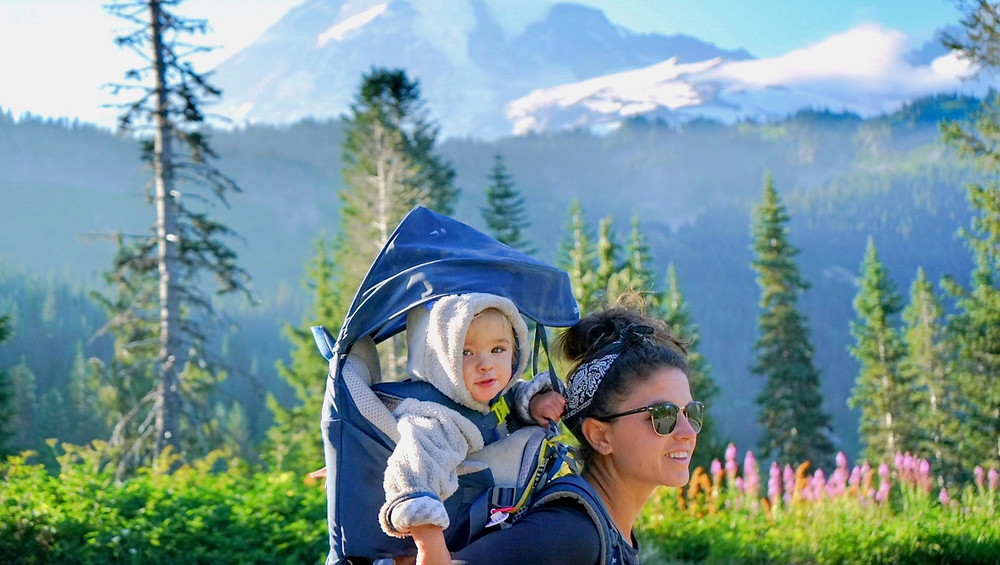 Mother hiking with a mountain in the background and a hiking carrier on her back with here daughter