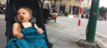 Baby with no shirt in a stroller while traveling