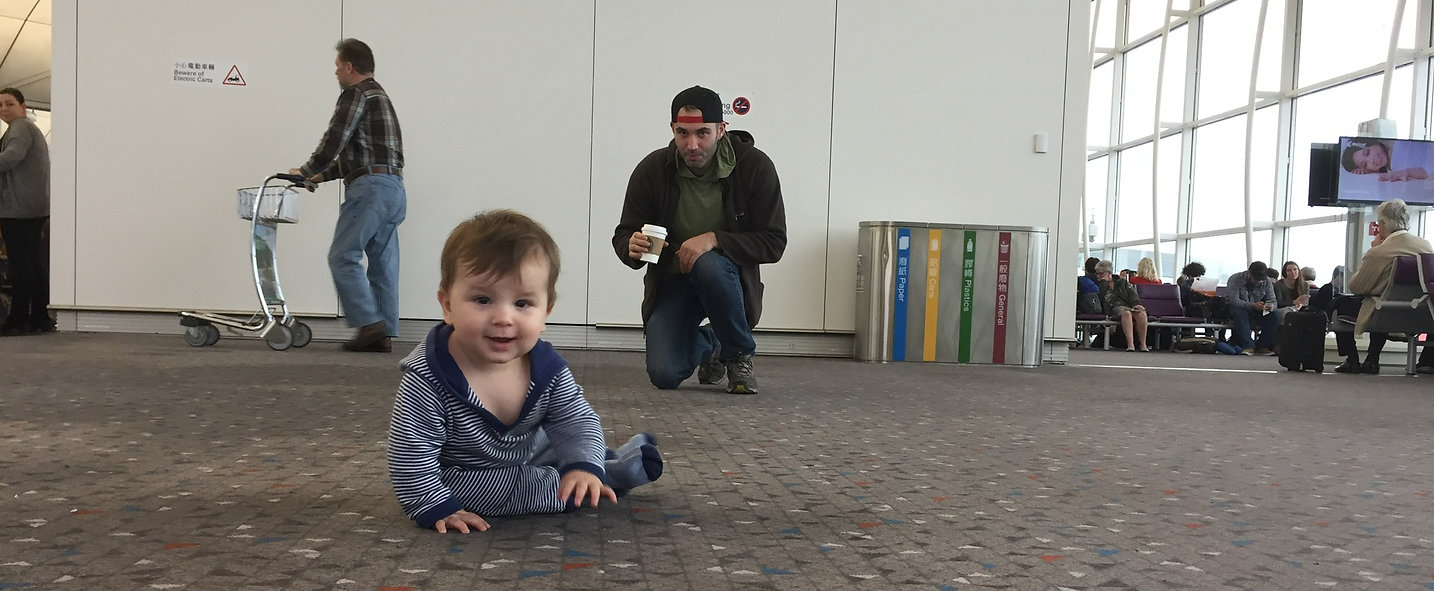 Our son crawling around the airport with his father looking on
